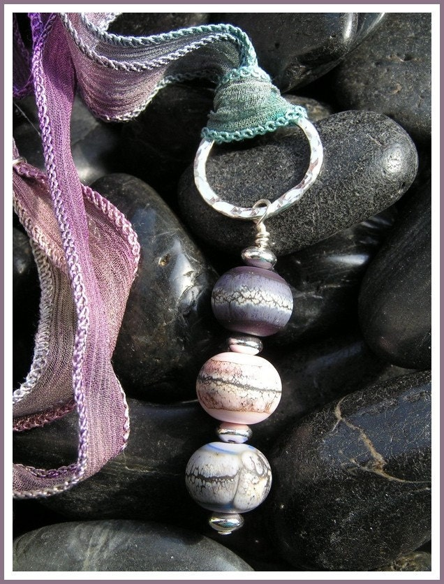 Beautiful etched beads dangling from a sterling hammered ring, worn on a hand-dyed silk ribbon