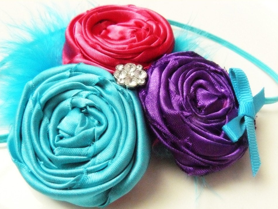 Bright and Fun. Turquoise, Hot Pink, and Vibrant Purple Rosette Trio With Center Rhinestone Accent and Added Marabou. Comes attached to a skinny turquoise headband.