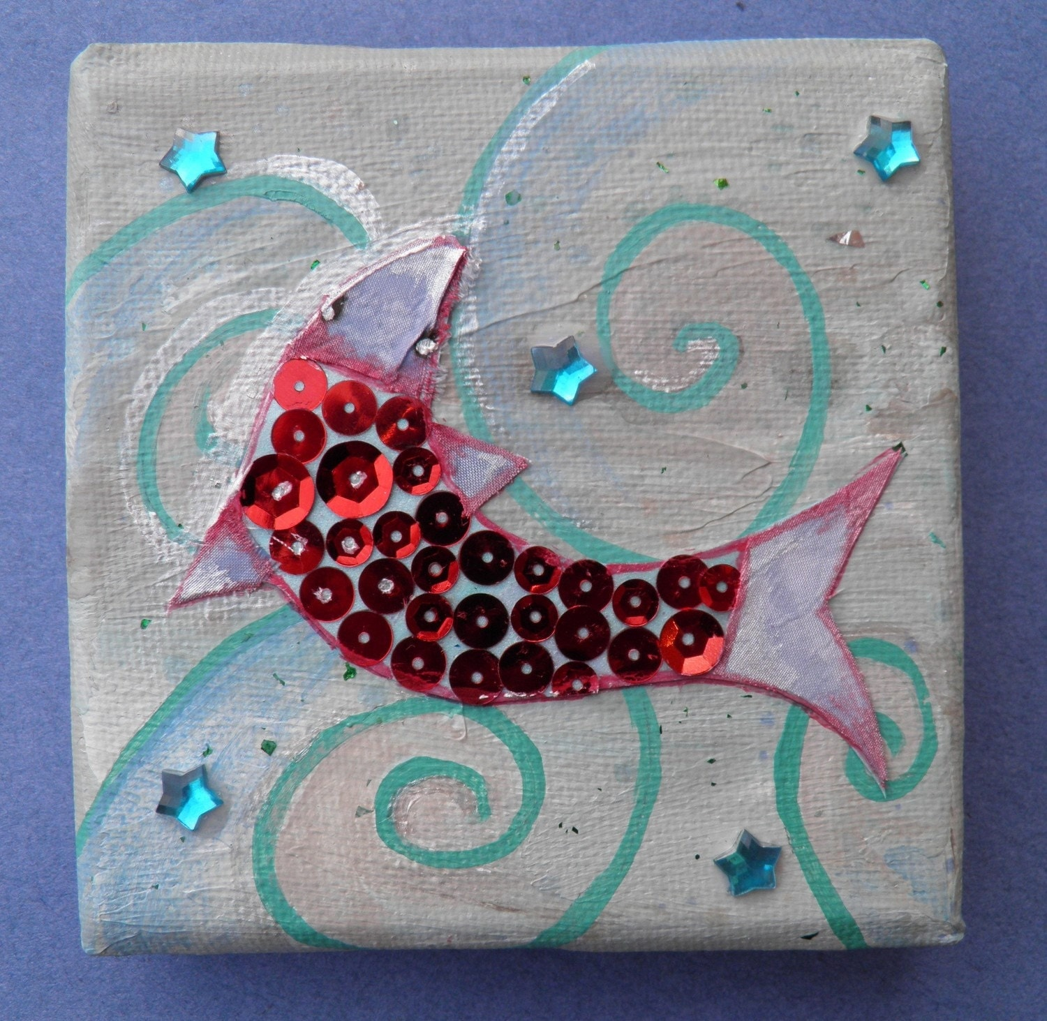 Little sequin fish on painted canvas