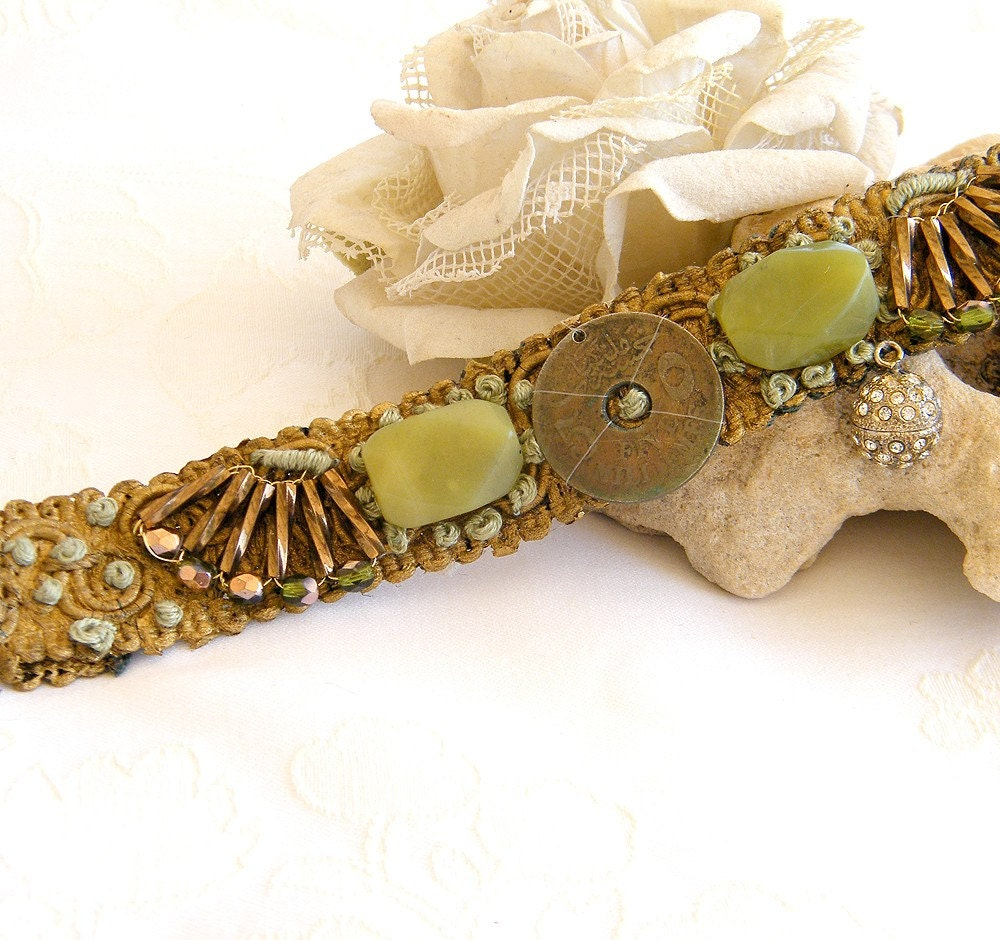 Mintook- Vintage Bracelet, with middle antique copper old coin, 2 green jade stons, verious golden beads and more, all stitched to a ribbon lace.