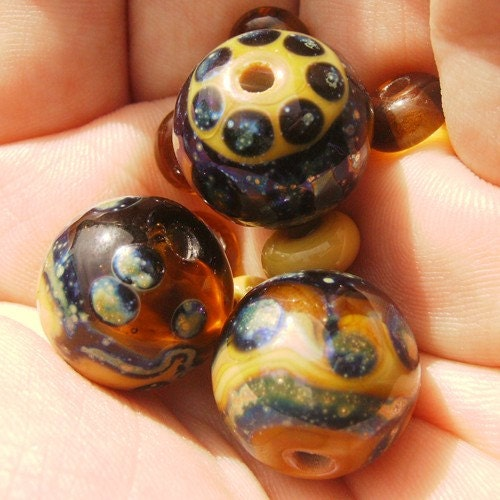 Honey Shimmer is a clear honey and opaque sandstone lampwork mini bead set with glittering oil slick dot and line decoration