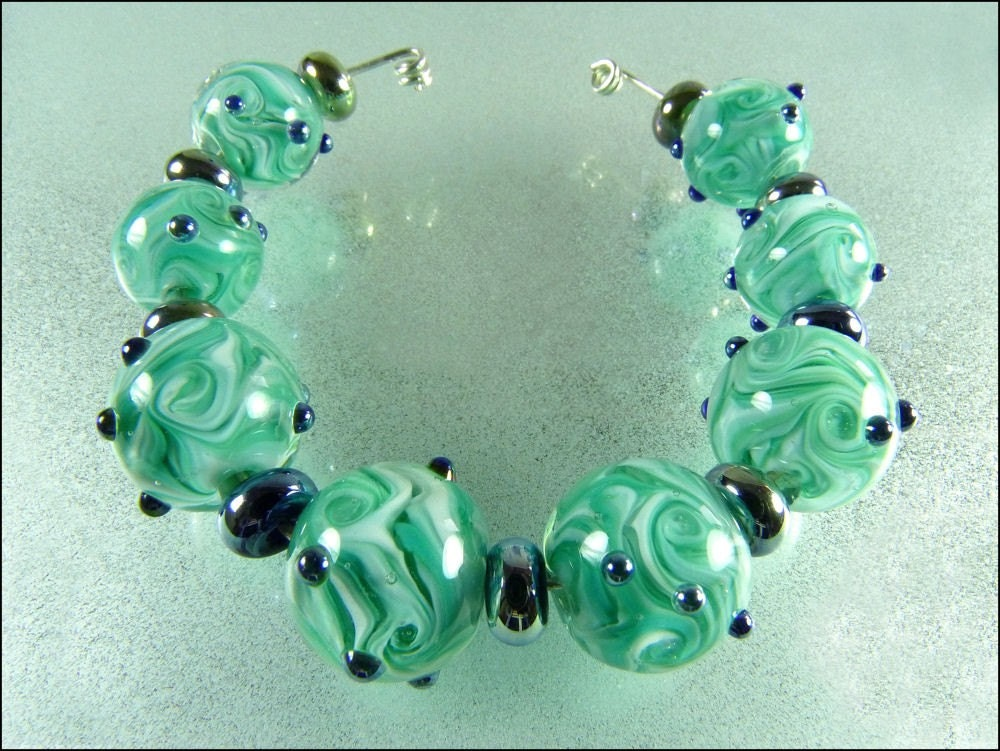 The round beads are a swirly mixture of teals and white encased with crystal clear glass