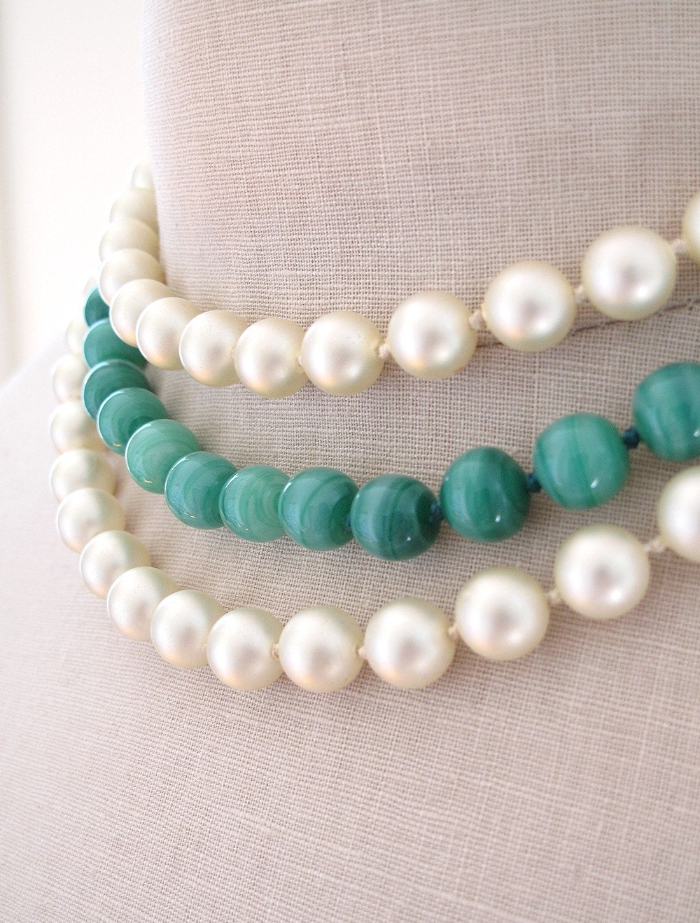 This beautiful three strand necklace sits close to the neck. It is made of two strands of pearls and one strand of green glass beads that resemble Jade. The most beautiful feature of this necklace is the ornate gold clasp with a green bead set in the center. The clasp is 1.25