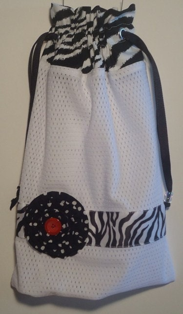 White mesh pointe/ballet shoe bag.  Zebra print topper with zebra print wide ribbon and white poka dots on black rosette flower.  Black drawstrings with beads for easy closer.