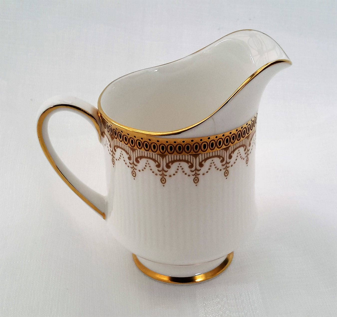 Paragon Athena creamer or milk jug fine bone china made in England by appointment of Her Majesty the Queen. White and gold china jug.