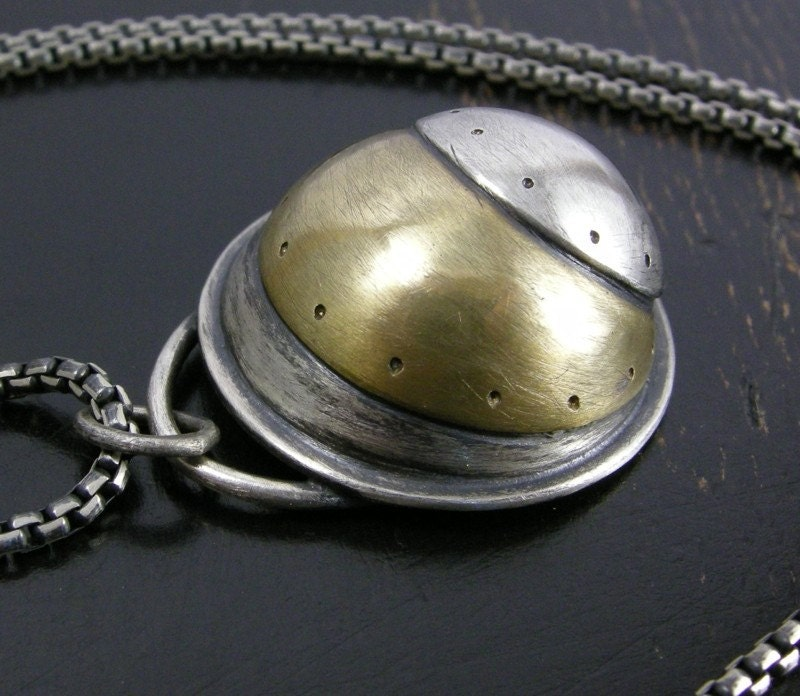 Sterling silver and brass hollow pendant.