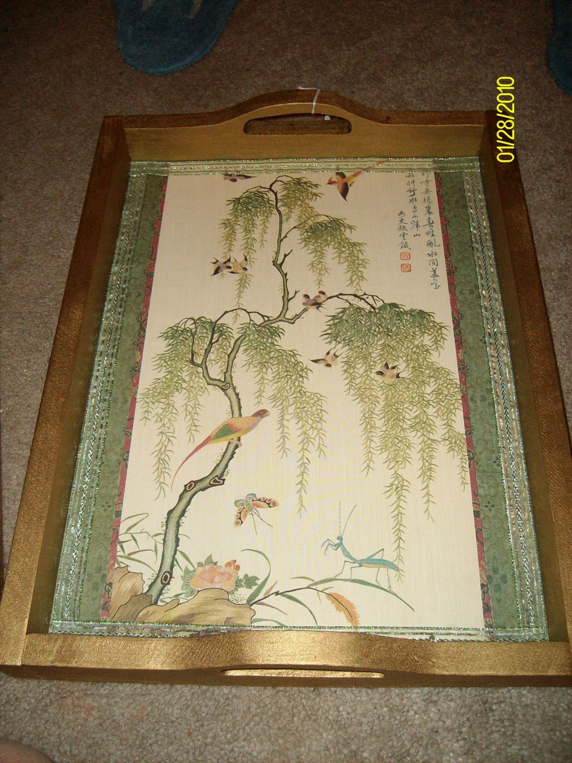 This is a beautiful wooden tray that has been painted gold and has an oriental design wallpaper on the bottom. I bought this tray at a yard sale and painted