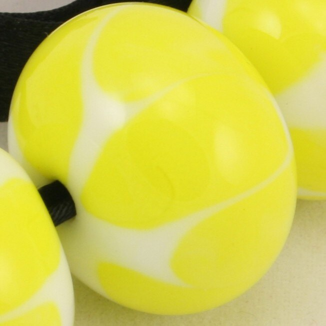 A set of 7 lampwork glass beads in bright yellow and white.