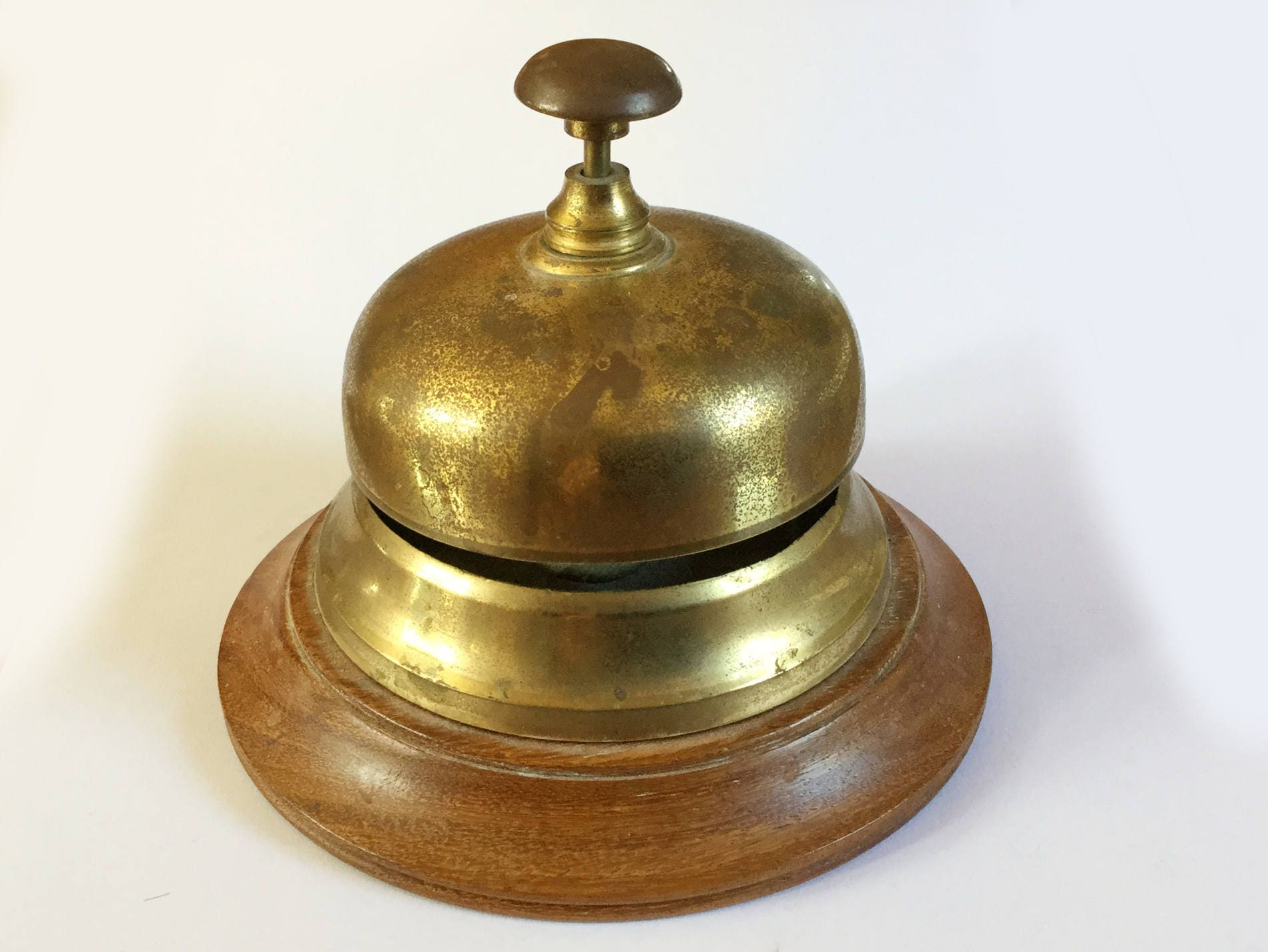 Vintage brass and wood desk hotel reception bell Round base Distressed worn metal