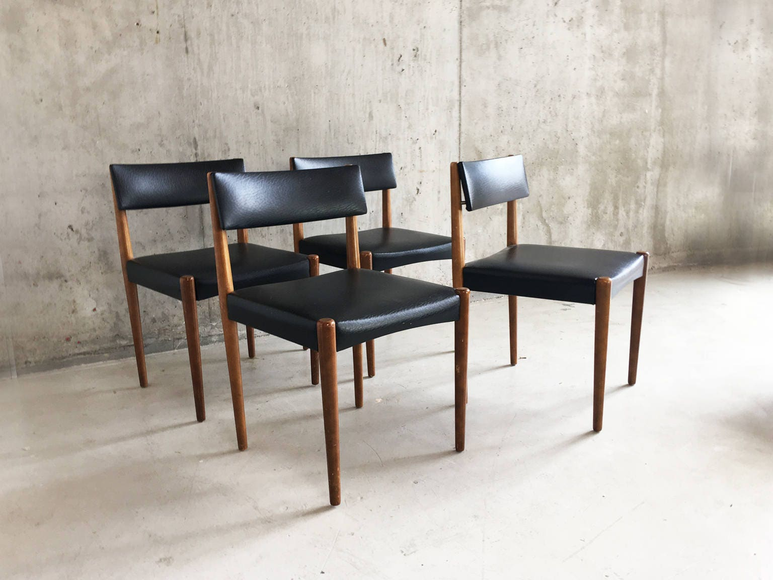 Set of four 1970s mid century teak and black vinyl dining chairs