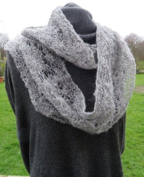 Light grey handspun alpaca infinity scarf in a lacy daisy pattern.