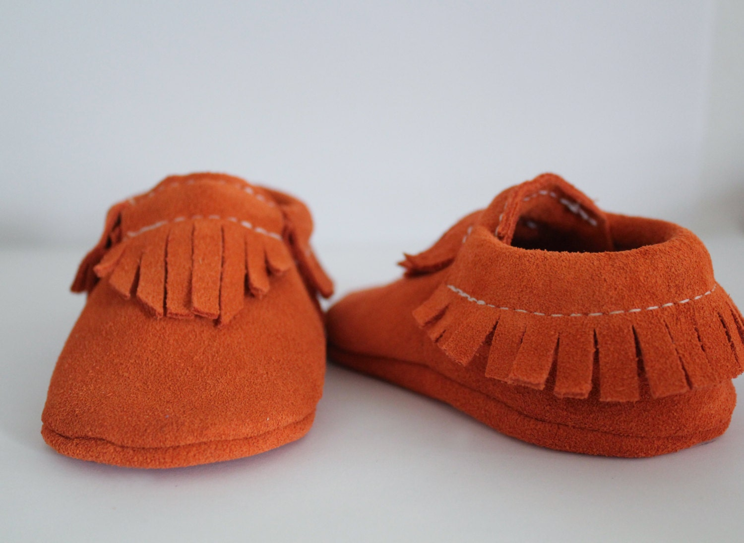 Orange suede baby moccasins