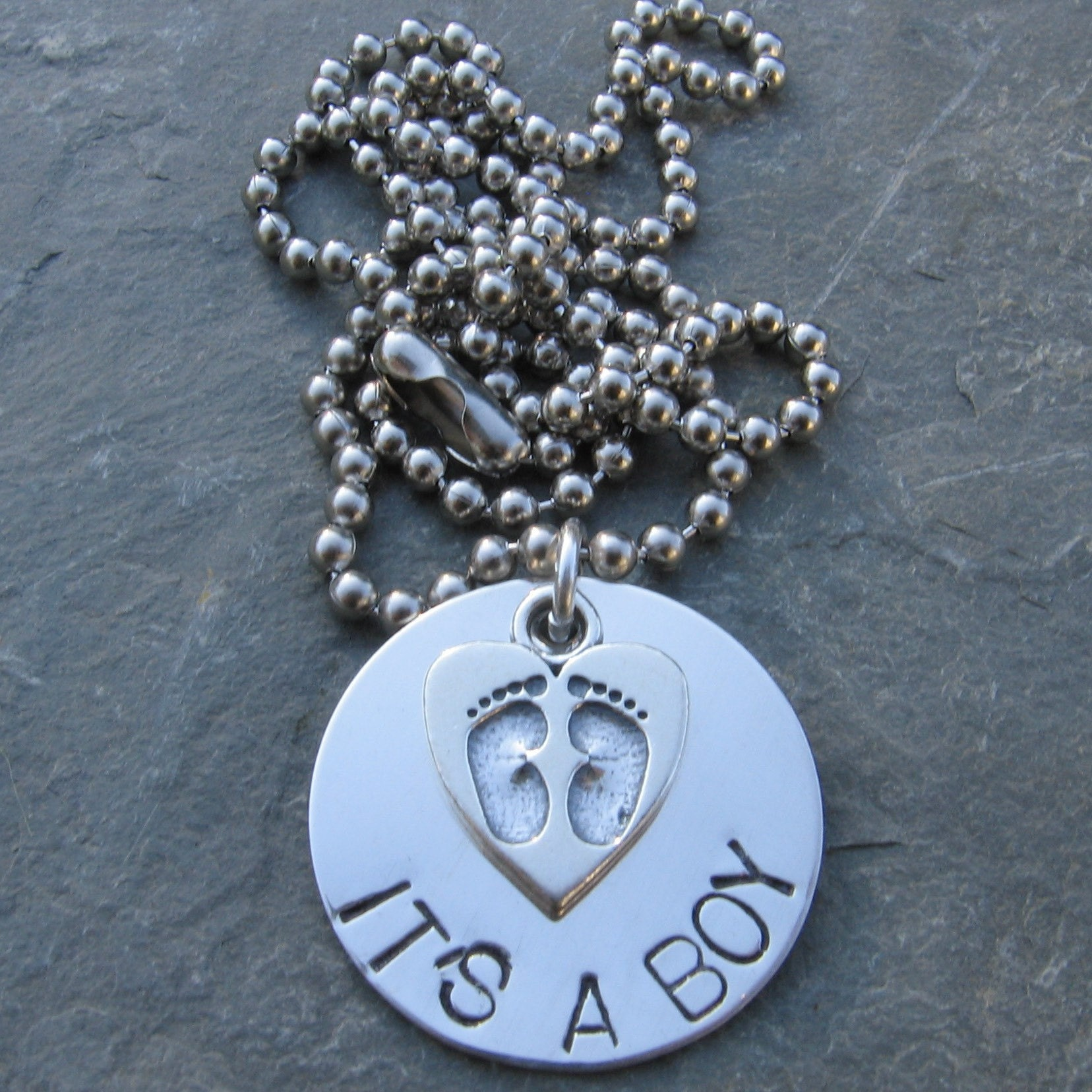 It's a boy / girl necklace, sterling silver disc hand stamped and personalized with heart baby feet charm