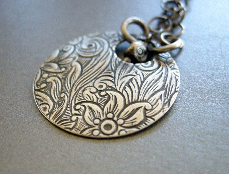 handmade necklace with embossed flowers on oxidized sterling silver