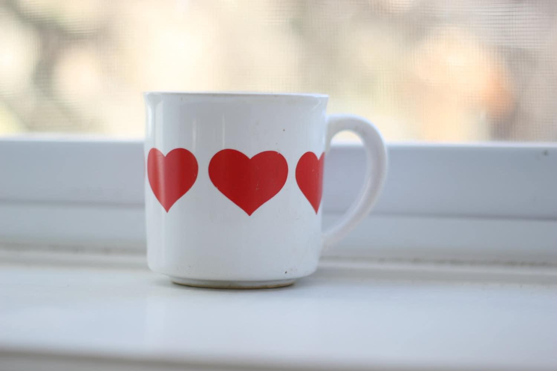 Corações vermelhos em caneca de café branco.  Café da manhã perfeito no Dia dos Namorados.