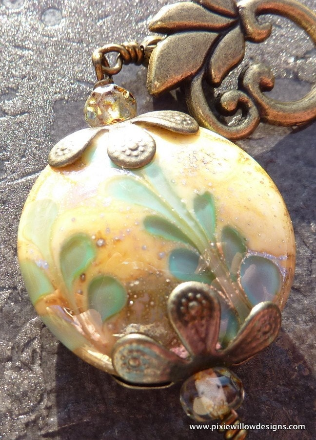 A fabulous detailed lampwork bead in tones of gold.