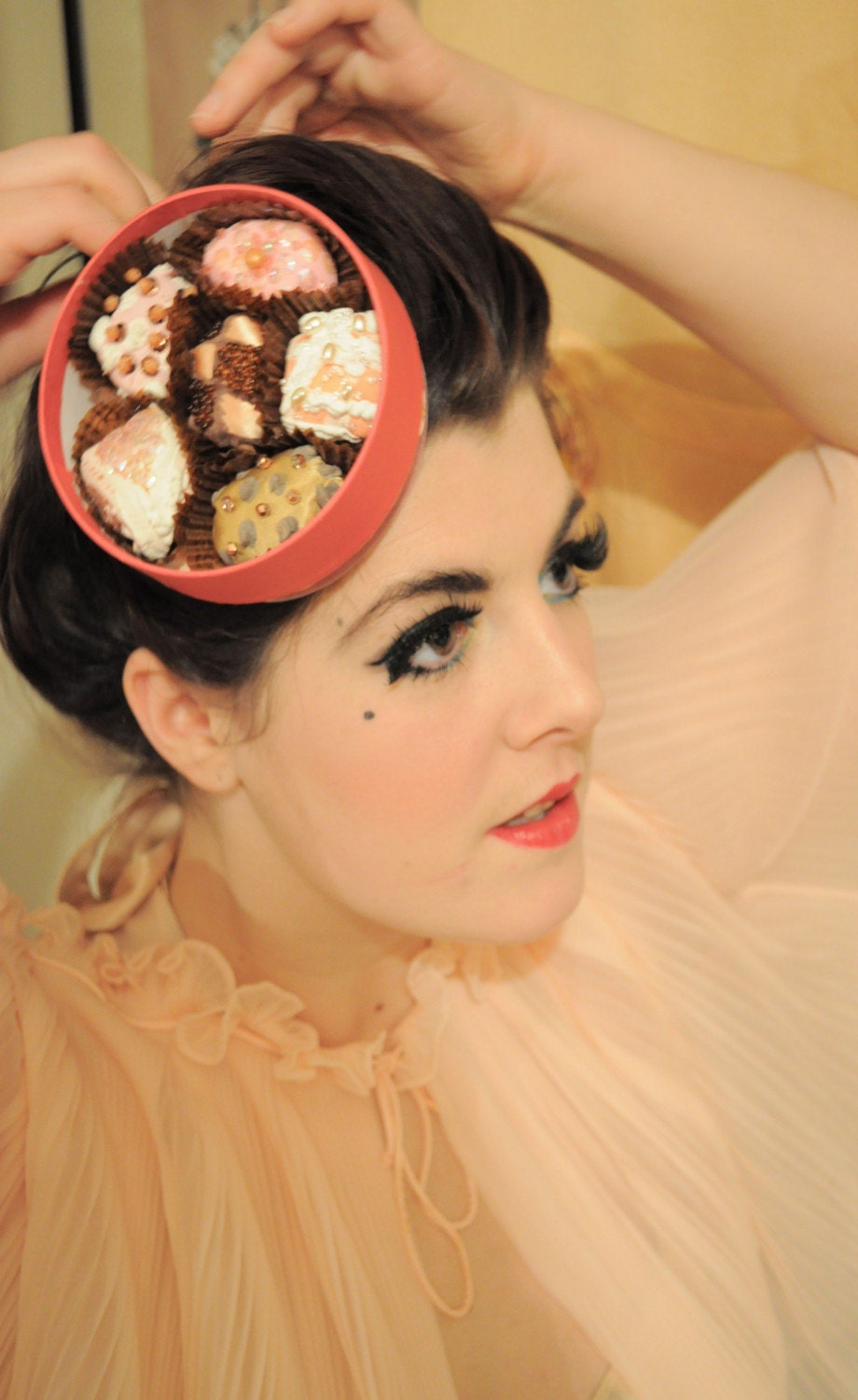 A cerise pink round 'Chocolate box' fascinator hat, hand printed and beaded using vintage fabrics.