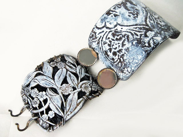 Spohia and the Gnostics.  White Patina Cuff with stamping over cowhide, etched salvaged tin and mirror buttons.