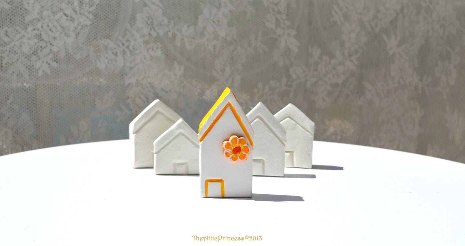 Miniature white clay house with yellow flower, spring home decoration
