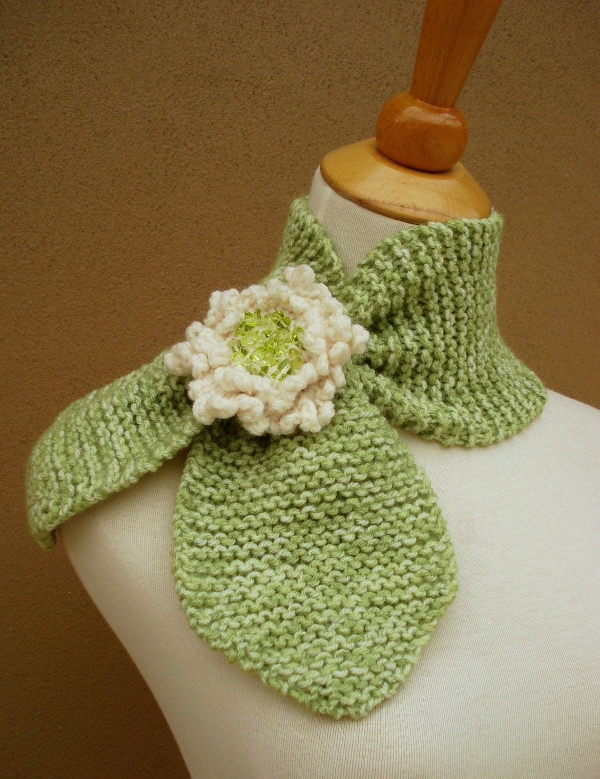 Green knit scarflette with white brooch, via Etsy: gsakowskidesigns