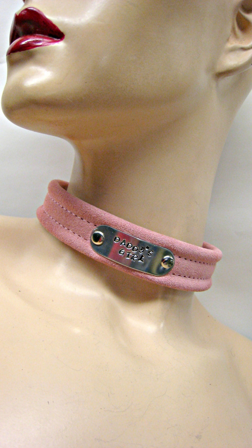 Weighs solid pink bondage collars and leads