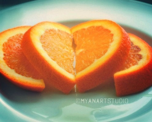 orange slices arranged like a heart on a green plate