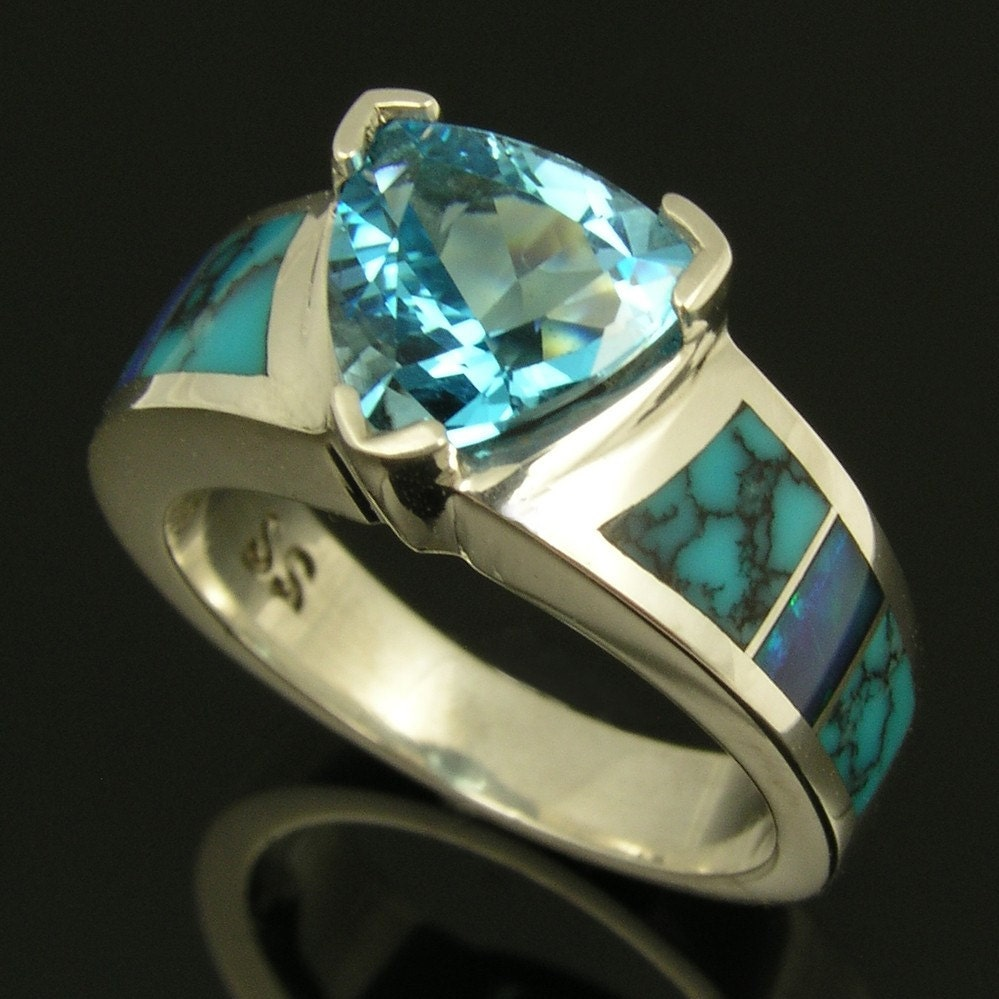Sterling silver ring with a 225ct trillion cut blue topaz and inlaid with