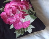 Black cushion with large bright pink embroidered flower.