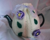 Hand Knitted cream tea cosy with purple/lilac flowers and green leaves. UK seller