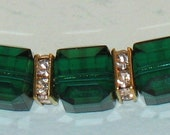 Gold tube bracelet with emerald swarovski crystal cubes and squaredells