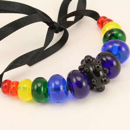 A Graduated set of 13 lampwork glass beads in a Rainbow of transparents, with a deep violet bumpy focal bead.