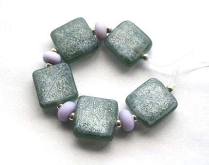 5 Grey lampwork tile beads with a scattering of white enamels and fine stringer pattern in pale lilac accompanied by 4 pale lilac spacer beads