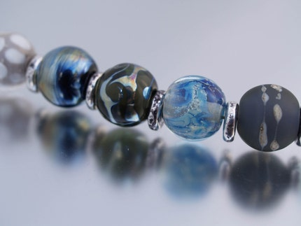 eight handmade glass beads in icy shades of blue and grey