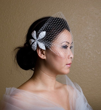 A fullyfeminine French tulle birdcage veil and handsculpted bead flower