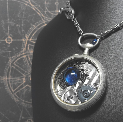 A very neat necklace made of clock parts and jewels inside a pocket watch that's attached to a necklace.