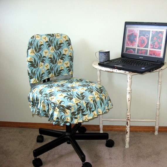 Picture of a handmade Office Chair Slip Cover on an office chair, for sale www.etsy.com, the chair is in front of a small table with a lpatop and a mug on it, representing a home office