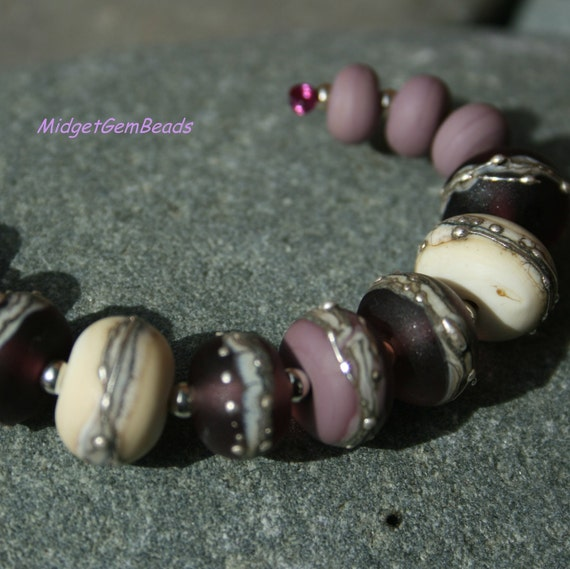 Rich purples combine with stone like ivory in this set of beads.