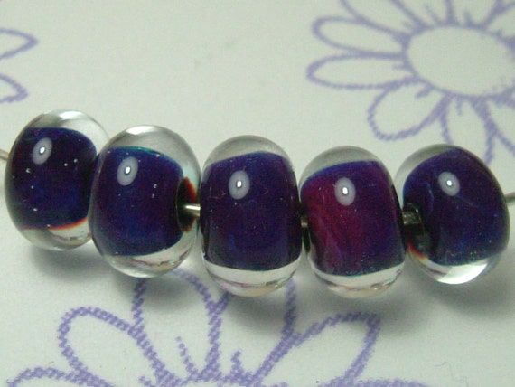 A set of 5 beads, made using reactive glass which has given shades of mainly purples and blues. Encased with a thick layer of crystal clear glass.