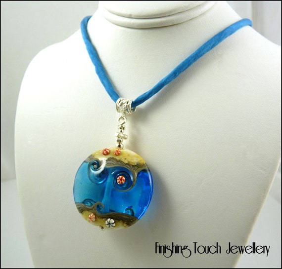 This is a gorgeous lampwork pendant made by me from transparent aquamarine with ends of silvered ivory.
