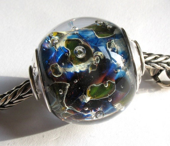 This beautiful silver cored lampwork bead has greens and shimmery silver and purple/blue trails.