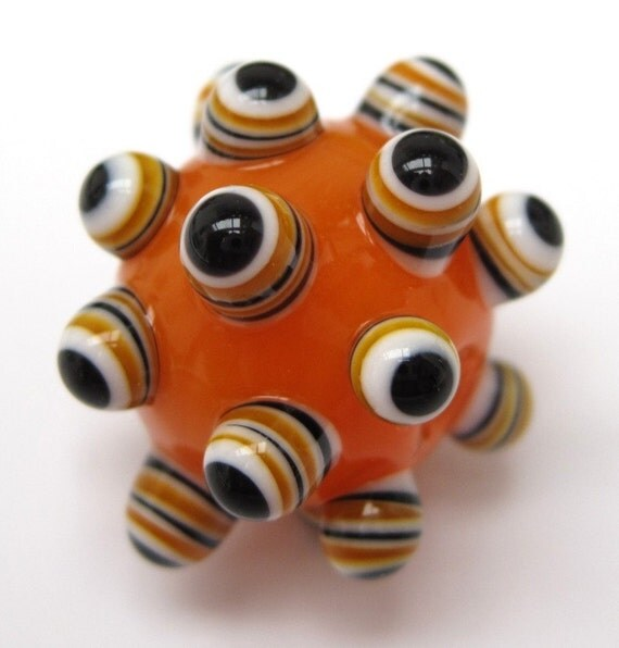 On a base of bright translucent orange there are stacked dot bumps of black, white and orange
