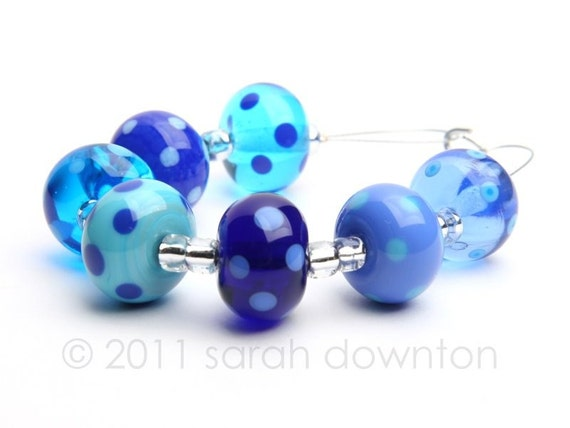 set of 7 beads in transparent and opaque blues and turquoise all decorated with coordinating colour dots