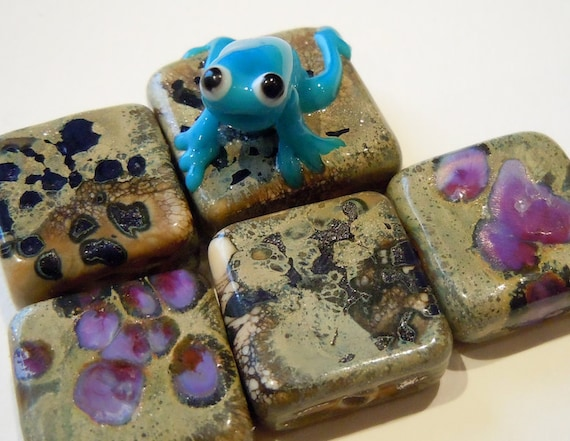 This a gorgeous set of lampwork beads, that come with a little guy who  needs a home. He is a bit startled, but I'm sure he will chill out when  he meets his new owner!