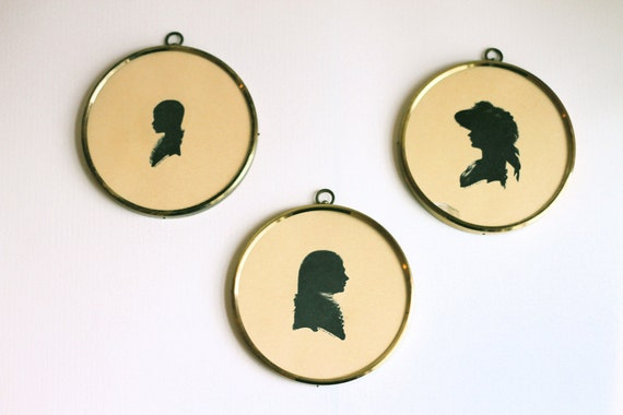 Family of three Silhouetted Profiles in round brass Frames