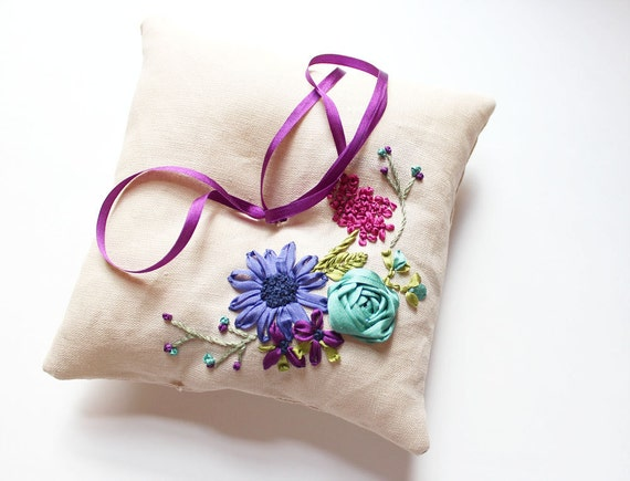 Ring pillow with ribbon embroidered flowers in teal, purple, and magenta