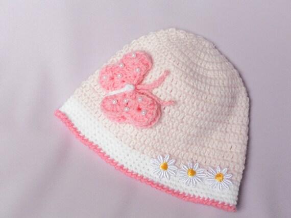 کلاه Crocheted برای یک نوزاد در صورتی نرم را با یک پروانه زیبا