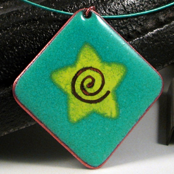 A stunning turquoise and lime green enamel on copper pendant with a star motif and a polished copper edge.