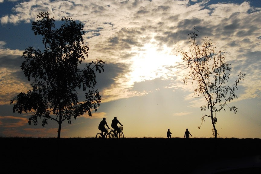 Two bicycle riders are silhouetted at Sunset in Zagreb, Croatia.