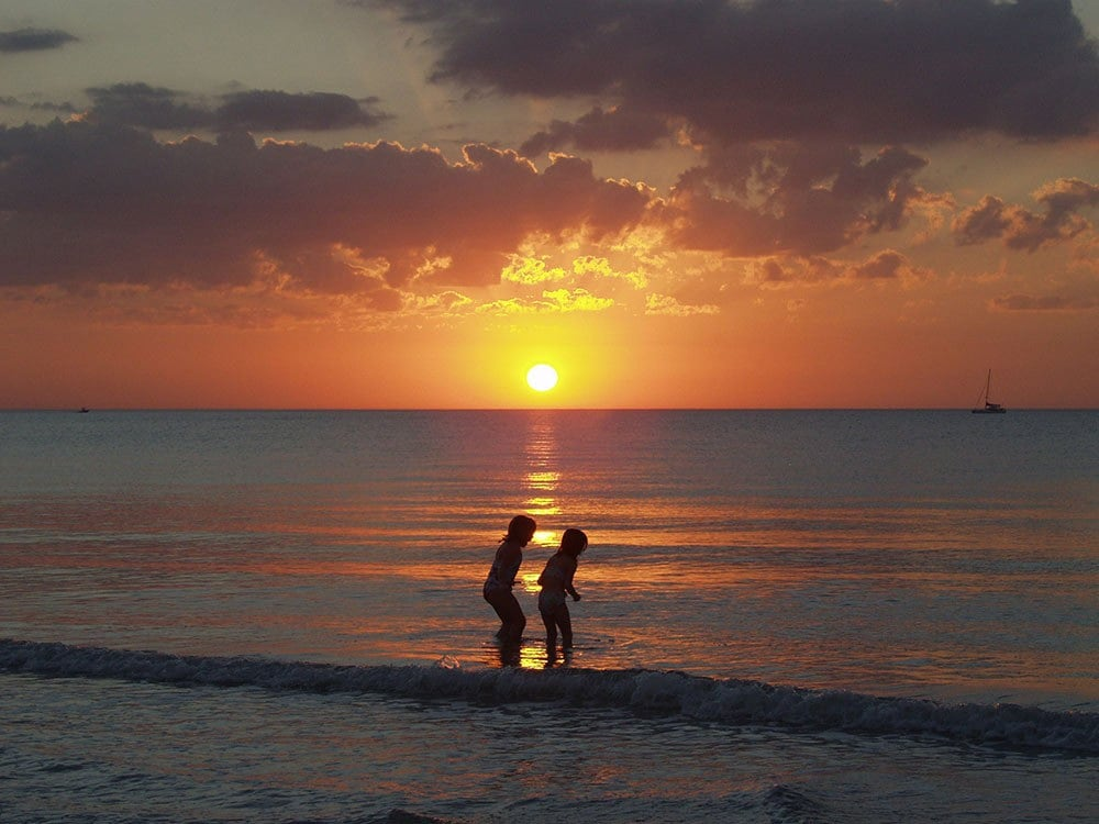 children silhouetted playing on a beach at sunset