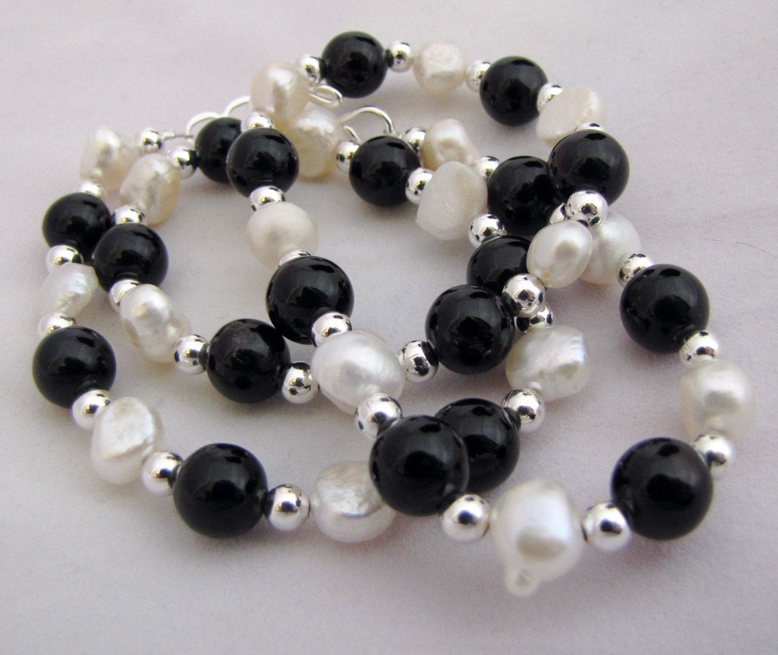 necklace made of irregular pearls and 6mm black onyx beads, separated by 4mm silver plated brass beads